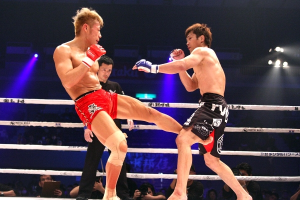 A 25-year old ISAO (left) finished UFC veteran Kuniyoshi Hironaka (right) with a soccer kick to the head to improve his pro MMA record to 15-1-4.